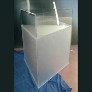 Cette vitrine triangulaire sur piédestal en plexiglas continue la forme de sa base en plexiglas satiné. Forme insolite qui se fait remarquer