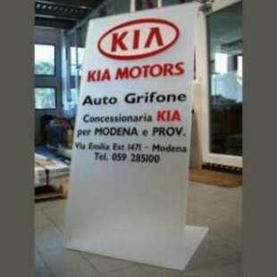 """Panneau publicitaire plexiglas autoportant salon auto Kia, en bi-satiné 10 mm. Plié à """"L"""". Autoportant. Lettrage publicitaire en PVC adhésif."""