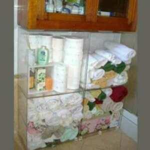 Meuble à cubes plexiglass pour linge de bain, 4 cubes de taille égale, à 5 côtés, placés sous un meuble accroché dans une salle de bain.