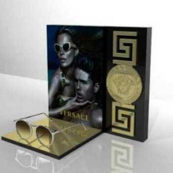 Espositore plexiglass occhiali Versace in oro specchiato per il marchio con marcatura laser, le greche in rilievo e la stampa grigio scuro