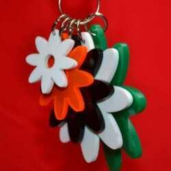 Vue de prés du Porte-clés multifleurs plexiglas de couleur, 5 fleurs de tailles différentes, pour les attacher à des sacs à main ou à des sacs pour filles.