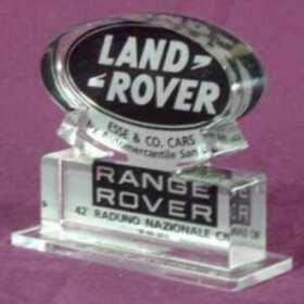 Targa plexiglass logo Land Rover su trasparente con marchio tagliato al laser. Il logo stampato, sagomato anche lui, è applicato sul retro