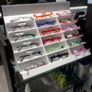 Présentoir porte lunettes plexiglas blanc points de vente lunettes marque internationale GrandVision, incliné à casiers, pour 18 paires