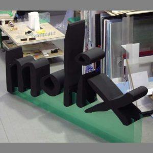Enseigne polystyrène peint grande épaisseur, du 40 cm. Lettres peintes en noir. Support à rampe plexiglas transparent où elles seront fixées