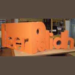 Enseigne polystyrène à angle droit stand expo très articulée. Un côté logo en positif et de l'autre logo en négatif. Peint d'un joli orange.