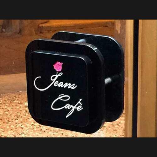 Pommeau de porte plexiglas massif noir pour boutique, carré noir brillant coins arrondis. Il est assorti au panneau noir dans la vitrine.