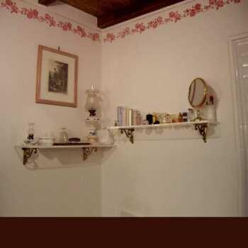 Étagères murales plexiglass massif 25 mm sur supports en laiton doré, ambiance douillette dans une salle de bains d'une maison de campagne.
