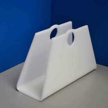vue de 3/4 du Porte-revues en plexiglas opale forme de sac, in 10 mm. Les magazines sont rangés à portée de main. Fini les piles sur la table de salon!