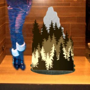 Décoration vitrine en plexiglas personnalisé Moncler. Base noire, devant forêt imprimée de sapins sur plexi, derrière plexi Frost effet glacé