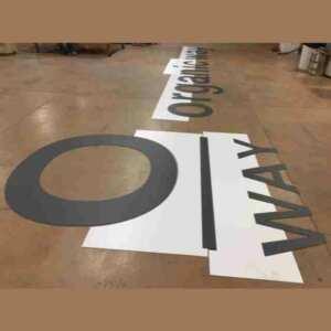 Enseigne PVC noir à lettres détachées montée grâce à son gabarit. Le gabarit a la forme de la partie inférieure des lettres et reprend l'espacement de l'écriture