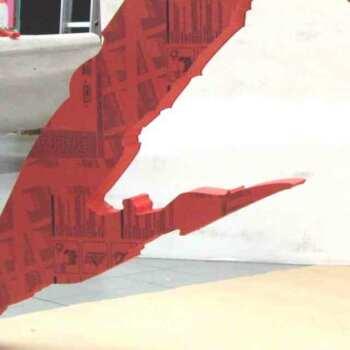 Insegna a logo PVC gigante rossa In PVC massello realizzata in una lastra intera fresata, destinata ad essere appesa in aria su uno stand.