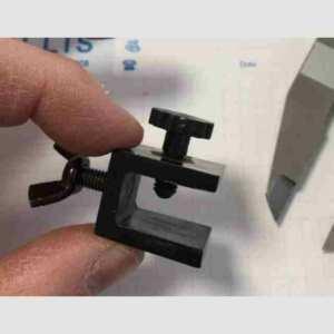 Mini morsetto in plexiglass nero con vite e farfalla accessorio per completare un espositore. Serve per foglietti informativi su i separé.