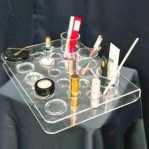 Présentoir plexiglass plié parfumerie en transparent perforé. Simple et efficace pour les différents produits d'une même marque