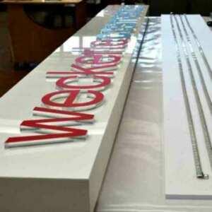 Enseigne plexiglas lettres en relief avec caisson opaque, en blanc et lettres en transparent de 15 mm découpées au laser,décorées en rouge