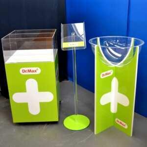 Porte dépliant ou porte brochure en plexiglass de sol avec le rappel des couleurs de la marque Dr. Max. Le socle rond, la tige et la poche A4 sont entièrement transparents