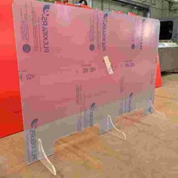 Cette protection en plexiglas double est réalisée sur mesure en une seule pièce, pour proteggere 2 réceptionnistes. Elle a 2 fenêtres passe documents